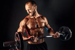 Hardy man doing exercise with heavy bar Stock Photos