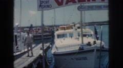 1961: a sport fishing vessel for charter is tied to a dock in a small harbor Stock Footage