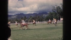 1961: men sitting on horses playing hockey on the grassy ground HAWAII Stock Footage