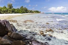 Low tide at Anse Severe in La Digue, Seychelles with palm trees and granite r Stock Photos