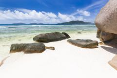 Anse Grosse Roche in La Digue, Seychelles with clear water and granite rocks Stock Photos