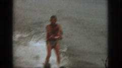 1961: two men ski in murky water from the back of a ski boat near a tree  Stock Footage