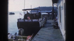 1961: man preparing to drive a boat docked in the water at a marina or boat Stock Footage