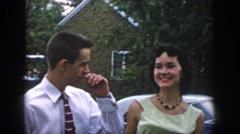 1958: a young man and a young woman nervously socialize outdoors near a car  Stock Footage