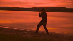 Man engaged in melee combat sports boxing at sunset sport shadow boxing Stock Footage