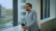A man standing in corridor holding and looking out the window Stock Footage