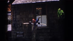 1958: pair of colorful parrots sit on perch in front of a brown shingle building Stock Footage