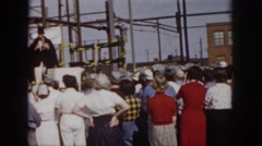 1958: people gathered around construction site black robe men giving safety Stock Footage