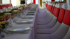 Row of chairs in the restaurant laid table with food celebration wedding video Stock Footage