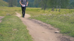 Male Runner. Tracking shot of male jogging and running on field Stock Footage