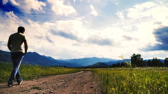 4K . Adult man tourist go on mountain hill in sunny day Stock Footage