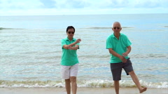 Asian elderly couple doing small exercise at sea beach Stock Footage