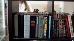 Female college student taking book from shelf in library and reading Stock Footage
