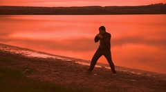 Man engaged in melee combat sports boxing at sunset shadow boxing sport Stock Footage