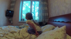 Girl watching TV in the bedroom on bed and constantly on the move. Time Lapse Stock Footage