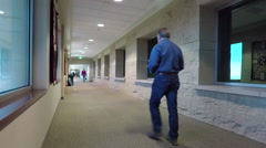 Cancer hospital long hall patient walking away HD Stock Footage