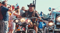 Biker with plaits making the hand horns sign while driving on his motorcycle Stock Footage