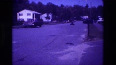 1981: neighborhood street in the 1960s with go-cart driving down the street away Stock Footage