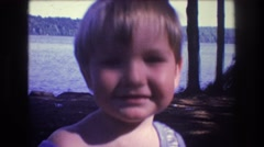 1975: a toddler sticker it's tongue out at the camera. BAXTER MAINE Stock Footage