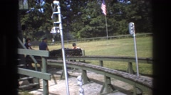 1975: two men and a baby riding a miniature train along a train track BAXTER Stock Footage