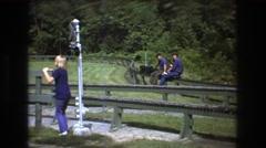 1975: park people walking jogging playing sliding greenery trees around Stock Footage