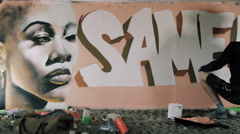 4K Young street artist using different paint mediums to create a mural on wall Stock Footage