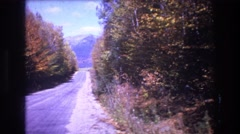 1975: distant view of a blue mountain down a sloping road  Stock Footage