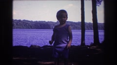 1975: baby walking looks happy waving pretty near water. standing on the ground. Stock Footage