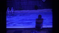 1975: a man is squatting on the bank of a swimming pool BOSTON Stock Footage