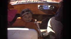 1975: kids in life jackets sitting in the front seat of a boat sailing through Stock Footage