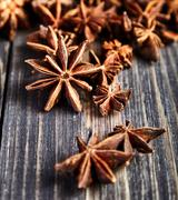 Heap of anise stars on wooden table Stock Photos