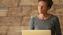 Woman thinking and using laptop computer Arkistovideo