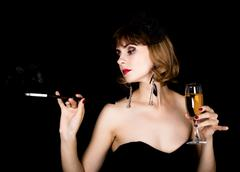 Beauty retro female model with professional makeup holding mouthpiece and glass Stock Photos