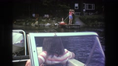 1975: person in life jacket on boat dock reels in boat  Stock Footage