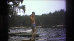 1975: man standing next to the lake, trying to decide to jump in or not. BOSTON Stock Footage