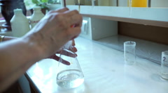 Hands in gloves mixes pink liquid and yellow liquid in flask in lab Stock Footage