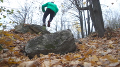 Man Jogging cross country And Jumping Over Obstacle running in forest and mou Stock Footage