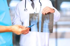 Healthcare, medical and radiology concept-Male doctors looking at x-ray of  foot Stock Photos