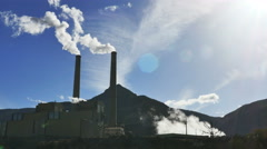 Back lit smoke steam from coal-fired power plant against blue sky Stock Footage