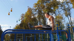 Athletic man exercise the abdominals on bar in city park. Healthy lifestyle Stock Footage
