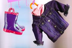 Multi-colored  rubber boots for kids hanging with jeans denim jacket Stock Photos
