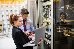 Technicians using laptop while analyzing server Stock Photos