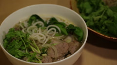 An adult using a chopstick to eat Vietnamese beef rice noodle, known as Bun B Stock Footage