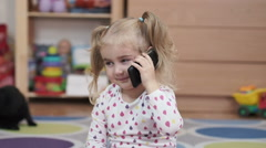 Little girl talking on a cell phone. child learns by telephone the good news Stock Footage