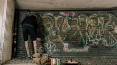 4K Time lapse graffiti artist using different pains to write his tag on wall Stock Footage