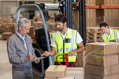 Warehouse manager and workers preparing a shipment Stock Photos
