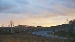 Timelapse-Setting sun lights rapidly moving clouds over mountain aspens road Stock Footage