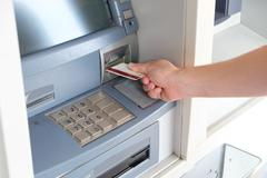 Man hand inserting a credit card in an atm Kuvituskuvat