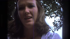1975: woman recording herself under a tree on a sunny bright day  Stock Footage