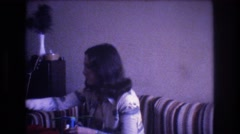 1975: woman sitting indoor playing with a toy BAXTER MAINE Stock Footage